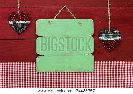 Blank green wood sign with fabric country hearts hanging on antique red rustic wooden background