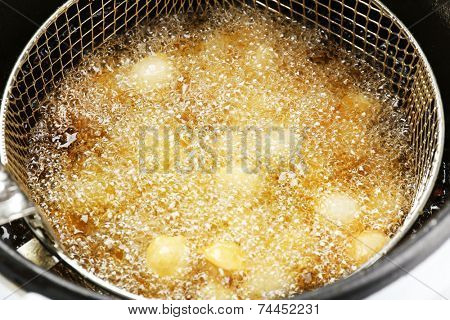 Dumplings in deep fryer, closeup