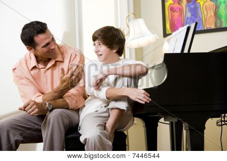 Father with teenage son at home smiling