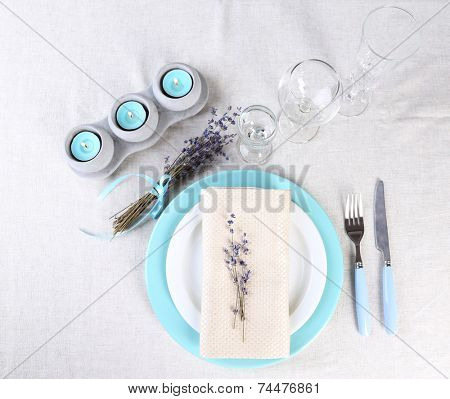 Dining table setting with lavender flowers on table, on light background