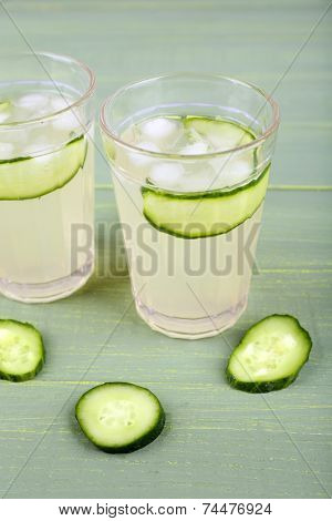 Two glasses of cucumber cocktail on wooden background