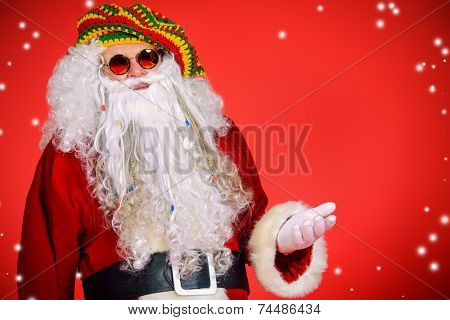 Portrait of a casual Santa Claus hippie over festive red background. Copy space.