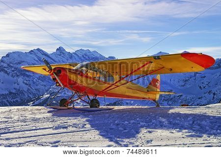 Yellow Red Airplane At The Mountain Airfield In Swiss Alps