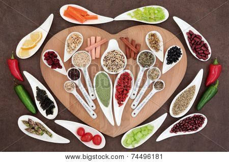 Large weight loss and diet super food selection in porcelain bowls and measuring spoons over brown paper background.