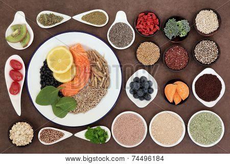 Large health food selection in bowls over lokta paper background.