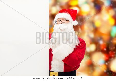 christmas, holidays, advertisement and people concept - man in costume of santa claus with white blank billboard making hush gesture over red lights background
