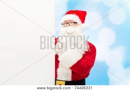 christmas, holidays, advertisement and people concept - man in costume of santa claus with white blank billboard making hush gesture over blue lights background