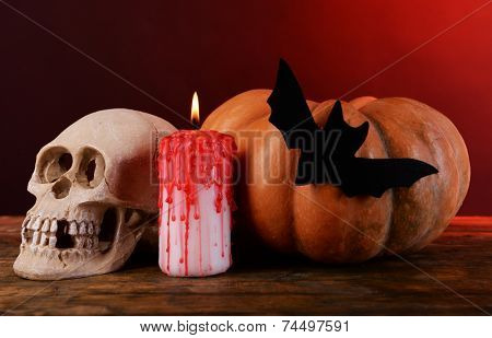 Composition of decorative skull, pumpkin, candle and Halloween decorations on wooden table, on dark color background