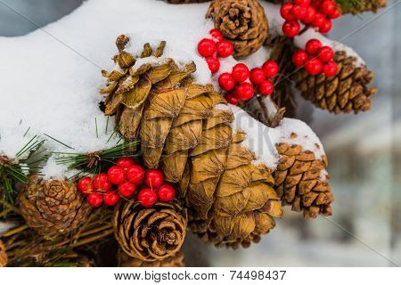 Detail of an outside Christmas cone wreath covered in snow