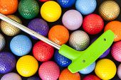 pic of miniature golf  - Green mini golf putter with balls of assorted colors - JPG