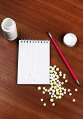 stock photo of prescription pad  - Writing Pad and the Pills on the Wooden Table closeup - JPG