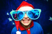 stock photo of fancy-dress  - Cheerful Kid in Big Glasses and Santa - JPG