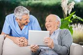 pic of male nurses  - Male caretaker and senior man laughing while using tablet computer at nursing home porch - JPG