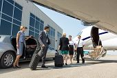 stock photo of jet  - Business professional about to board private jet while airhostess and pilot greeting them - JPG