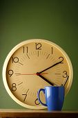 picture of analog clock  - Photo of an analog clock and a blue coffee mug - JPG