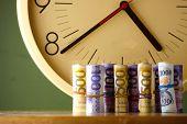 stock photo of analog clock  - Photo of an analog clock and rolls of paper money  - JPG