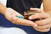 stock photo of viagra  - a young man with a bottle of pills in his hands - JPG