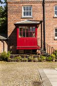 foto of rabbit hutch  - Vertical shot of old courtyard with redbrick house and iron steps leading to a red porch - JPG