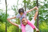 pic of southeast asian  - Father and daughter playing piggy back at outdoor garden park - JPG