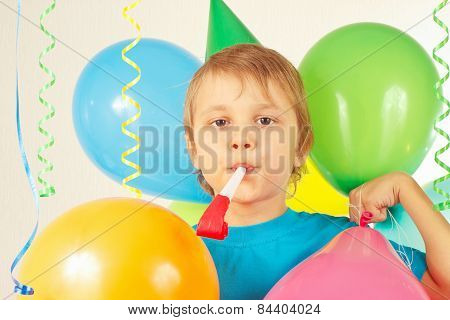 Little cute boy in holiday hat with whistle and festive balloons and streamer