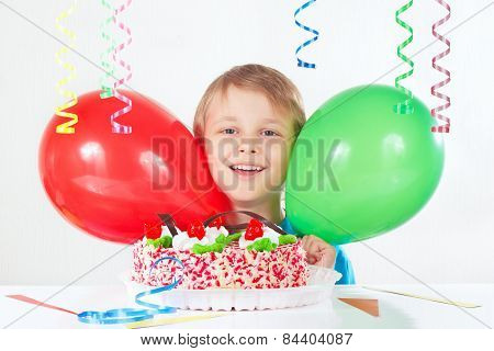 Little boy with a festive cake and balloons on white background