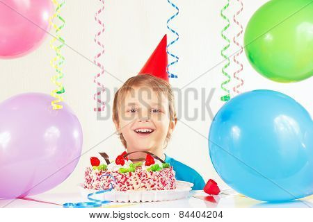 Young boy in festive hat with birthday cake and balloons