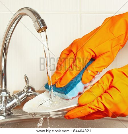 Hands in gloves with sponge wash the dishes under running water in kitchen