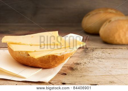 Bun With Cheese And Blurry Bread Rolls In The Background On Wood