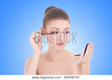 Portrait Of Young Beautiful Woman Applying Mascara On Her Eyelashes Over Blue