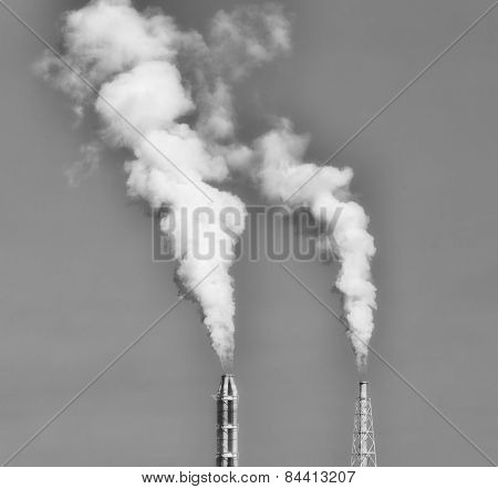 Blurred - Lant Stack With White Smoke Against Blue Sky In Black And White
