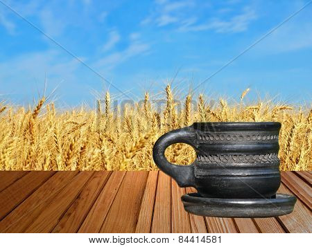 Black Tea Cup On Wooden Surface Against Of Golden Wheat.