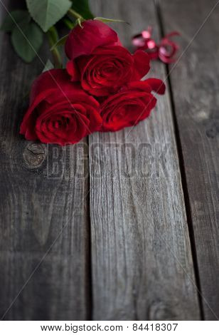 Three Red Roses On Rustic Table