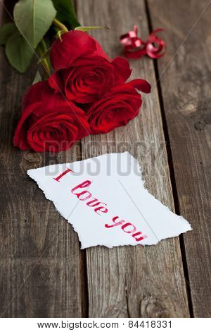 Three Red Roses On Rustic Table With Handwritten Words I Love You