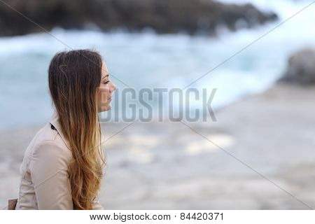 Profile Of A Pensive Woman On The Beach In Winter