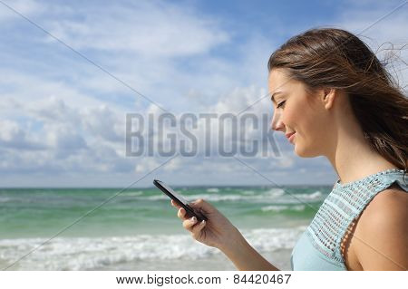 Profile Of A Girl Using A Smart Phone On The Beach