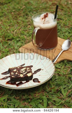 Iced Cocoa With Brownies On A Green Grass.