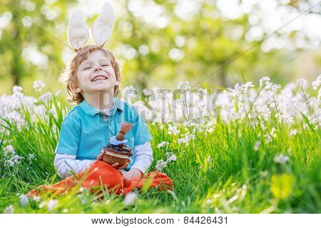 Cute Happy Little Boy Wearing Easter Bunny Ears And Eating Chocolate At Spring Green Grass