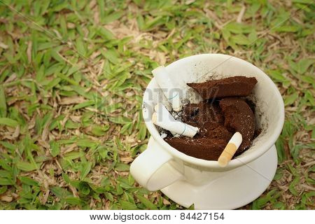 Cigarette In The Ashtray On A Green Grass.