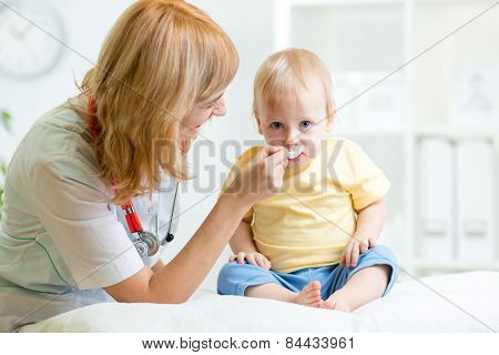 doctor giving medicament to kid with a spoon