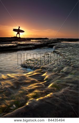Star burst behind a surfer going for a morning surf