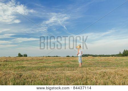 Teenage Farmer Standing On Harvested Field