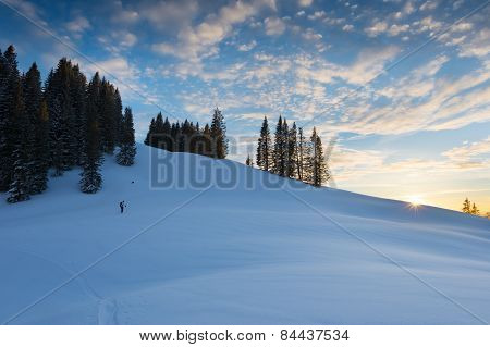 sunset at snowy hill with wonderful sky and trees at austria