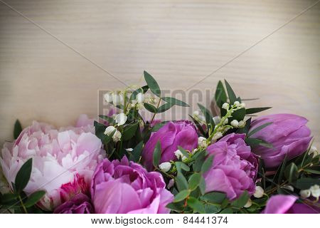 Pile Of Fresh Pink Tulips And Lily Of The Valley On Aged Wooden Table