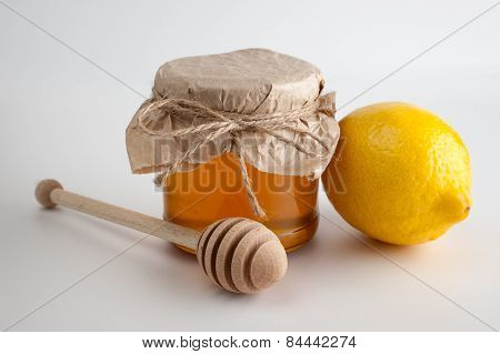 Honey In Jar And Lemon On A White Background