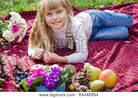 Beautiful little young baby lies on a red plaid. Lovely child smiling with bright flowers