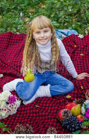 Beautiful little young baby in a pink hat with pear in hand. Beautiful child sitting on a red plaid.