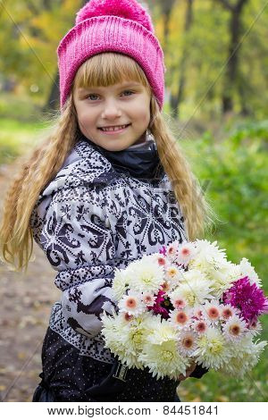 Beautiful little young baby in a pink hat with flowers in their hands