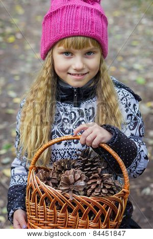 Beautiful little young little girl in a pink cap with a basket in his hands