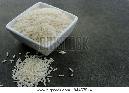 White Rice Spills Onto Black Cutting Board