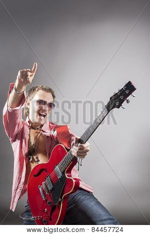 Music Concept: Portrait Of Expressive Caucasian Male Guitarist Playing The Guitar And Shouting Loud